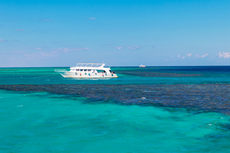 White yacht anchored near coral reef in Red sea, Egypt