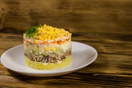 Traditional russian salad Mimosa on wooden table. Layered salad with sardine, onion, potatoes, carrot, cheese, eggs and mayonnaise