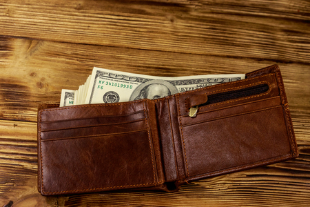 Opened wallet with american dollars on wooden table