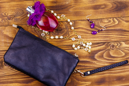 Women accessories on wooden background. Clutch bag, bottle of perfume, pearl necklace and earrings on wood table. Beauty and fashion composition. Top view, flat lay