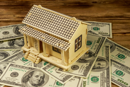 House model and U.S. one hundred dollar bills on wooden background. Property investment, home loan, house mortgage, real estate concept Stock Photo
