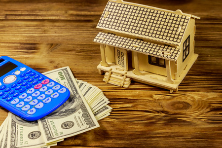 House model, U.S. one hundred dollar bills and calculator on wooden background. Property investment, home loan, house mortgage, real estate concept Stock Photo