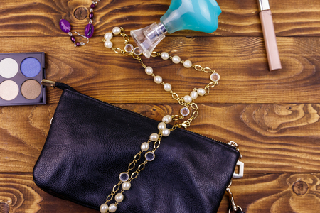 Women accessories on wooden background. Clutch bag, bottle of perfume, eye shadow, pearl necklace and earrings on wood table. Beauty and fashion composition. Top view, flat lay