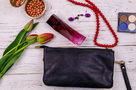Women accessories and make-up cosmetics on white wooden background. Clutch bag, perfume, eye shadow, rouge balls, necklace, earrings and tulips. Beauty and fashion composition. Top view, flat lay