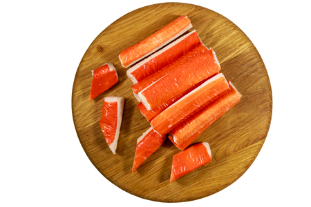 Crab sticks on wooden cutting board isolated on white background Stok Fotoğraf - 124775812
