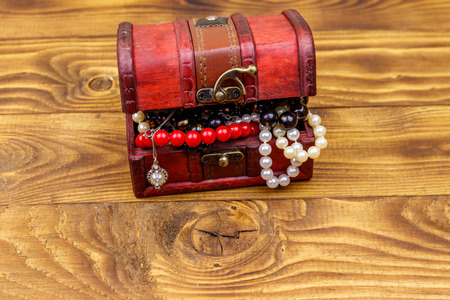 Vintage treasure chest full of jewelry and accessories on wooden background Stock Photo