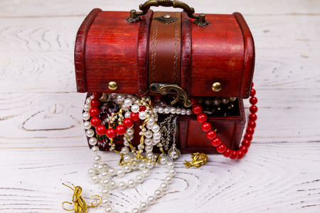 Vintage treasure chest full of jewelry and accessories on white wooden background