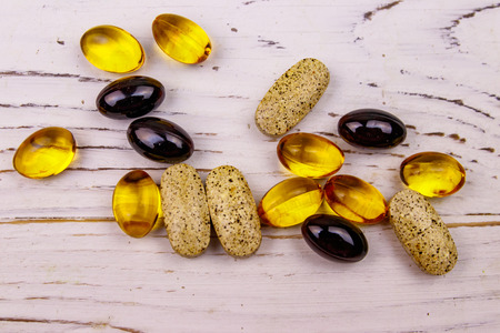 Mixed natural food supplement pills, omega 3, multivitamin capsules on a white wooden table Stock Photo