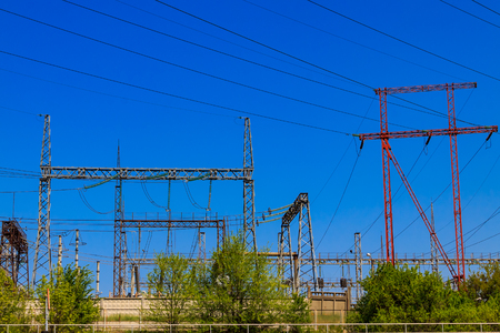 High voltage power lines towers on blue sky background