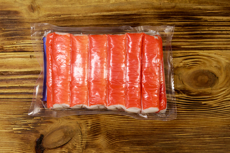 Crab sticks in vacuum pack on wooden table. Top view