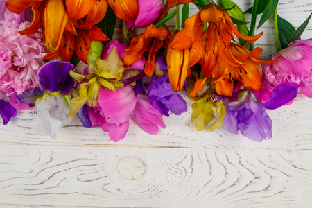 Bouquet of lilies, peonies and iris flowers on a white wooden background. Top view, copy space 版權商用圖片