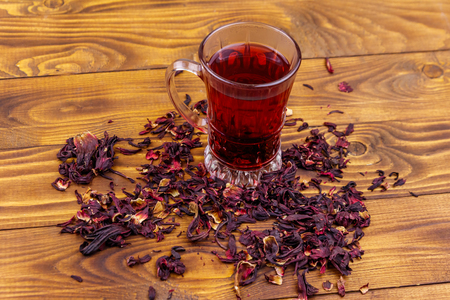 Glass cup of red hibiscus tea (carcade, roselle) on wooden table