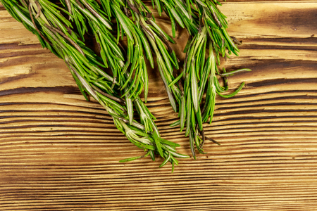 Fresh rosemary herbs on a wooden table. Top view Stock Photo