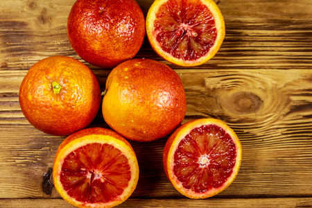 Red blood oranges on wooden table