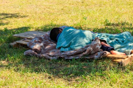 Homeless little boy sleeping on grass in city park. Poverty concept Stock Photo