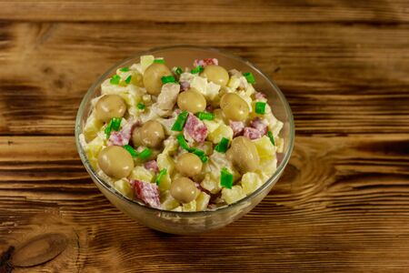 Potato salad with marinated mushrooms, sausage, onion and mayonnaise on wooden table