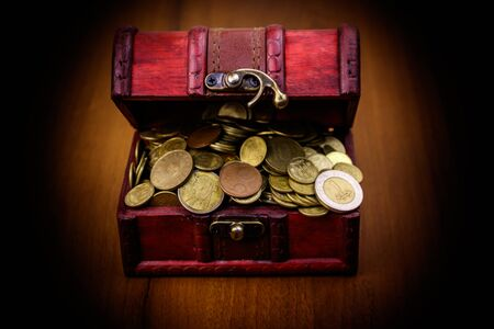 Vintage treasure chest full of golden coins on wooden background Stock Photo