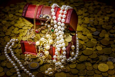 Vintage treasure chest full of gold coins and jewelry on a background of golden coins