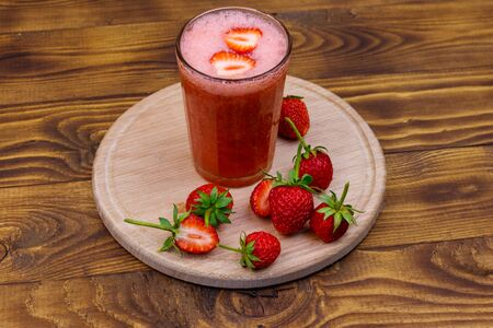 Glass of fresh strawberry smoothie on a wooden table