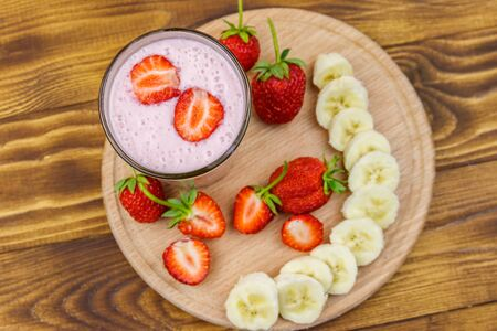 Glass of fresh smoothie of strawberry and banana on a wooden table. Top view