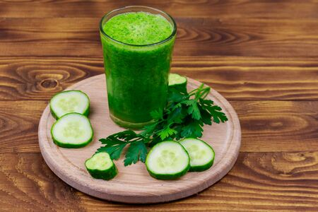 Glass of green detox smoothie of cucumber and parsley on a wooden table Reklamní fotografie