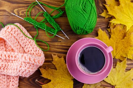 Cup of coffee, ball of yarn, knitting, knitted scarf and yellow maple leaves on wooden table. Autumn still life Stock Photo - 124773313