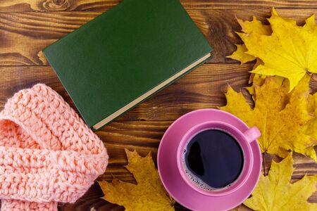 Cup of coffee, book, knitted scarf and yellow maple leaves on wooden table. Autumn still life 版權商用圖片