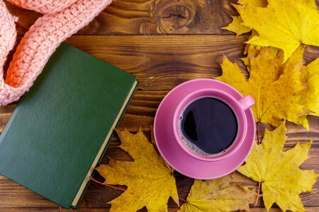 Cup of coffee, book, knitted scarf and yellow maple leaves on wooden table. Autumn still life Reklamní fotografie