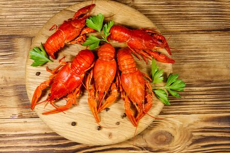 Boiled crayfish on cutting board on wooden table. Top view