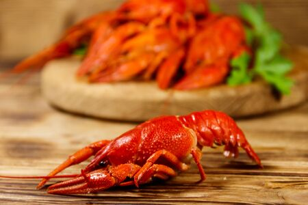 Boiled crayfish on cutting board on wooden table Stok Fotoğraf - 124773205