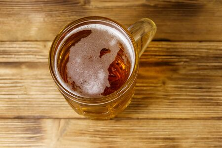 Mug of beer on a wooden table. Top view
