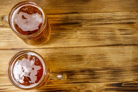 Two mugs of beer on a wooden table. Top view, copy space Stock Photo