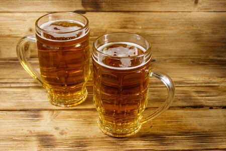 Two mugs of beer on a wooden table
