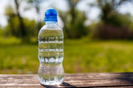 Plastic bottle with fresh drinking water on a wooden table on nature background