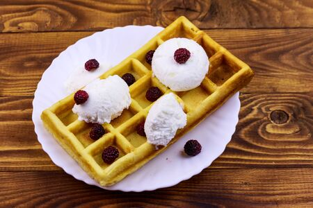 Belgian waffle with ice cream and blackberries on wooden table