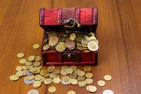 Vintage treasure chest full of golden coins on wooden background Reklamní fotografie