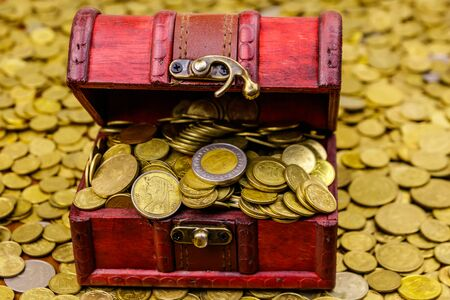 Vintage treasure chest full of gold coins on a background of golden coins