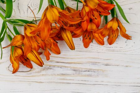 Orange lilies on a white wooden background. Top view, copy space