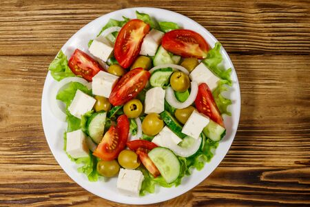 Greek salad with fresh vegetables, feta cheese and green olives on wooden table. Top view