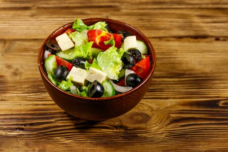 Greek salad with fresh vegetables, feta cheese and black olives on wooden table