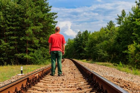 Lonely man walking on a railway track