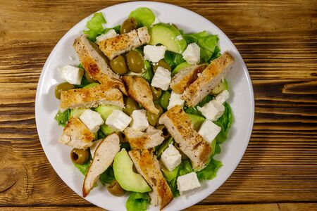Tasty salad with fried chicken breast, green olives, feta cheese, avocado, lettuce and olive oil on wooden table. Top view