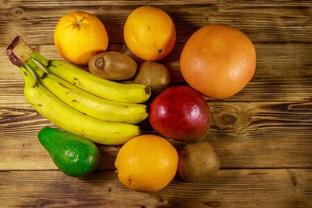 Assortment of tropical fruits on wooden table. Still life with bananas, mango, oranges, avocado, grapefruit and kiwi fruits. Top view
