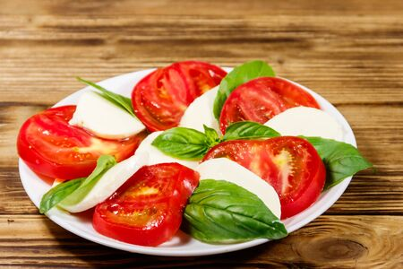 Italian caprese salad with tomatoes, mozzarella cheese and basil on a wooden table