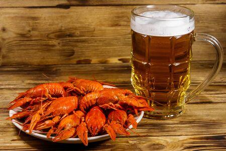 Boiled crayfish and mug of beer on a wooden table Reklamní fotografie