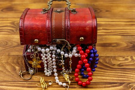 Vintage treasure chest full of jewelry and accessories on wooden background 스톡 콘텐츠