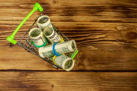 Small shopping cart with rolls of one hundred dollar bills on wooden background. Consuming concept Фото со стока