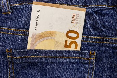Fifty euro banknote in the pocket of blue jeans