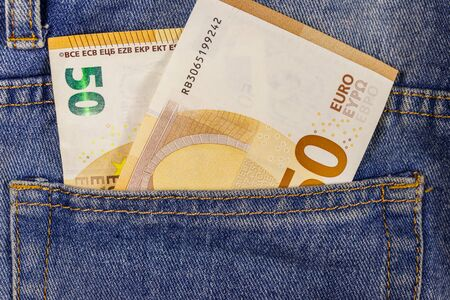 Fifty euro banknotes in the pocket of blue jeans