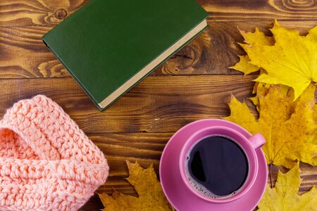 Cup of coffee, book, knitted scarf and yellow maple leaves on wooden table. Autumn still life Stock Photo